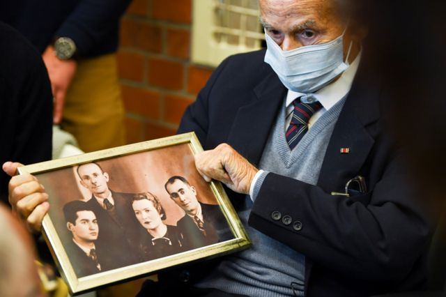 Holocaust survivor Leon Schwarzbaum holds a picture in the courtroom during a trial against a 100-year-old former security guard of the Sachsenhausen concentration camp, at the Landgericht Neuruppin court in Brandenburg, Germany, 7 October 2021