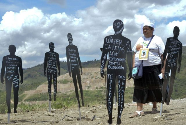 Mujer camina entre figuras de cartón negras que tienen algo escrito en tiza.