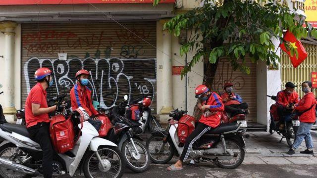 Shipper chờ đơn hàng dọc một con phố ở Hà Nội vào ngày 25 tháng 5 năm 2021 khi chính quyền mở rộng lệnh đóng cửa để ngăn chặn sự lây lan của coronavirus Covid-19 (ảnh minh họa)
