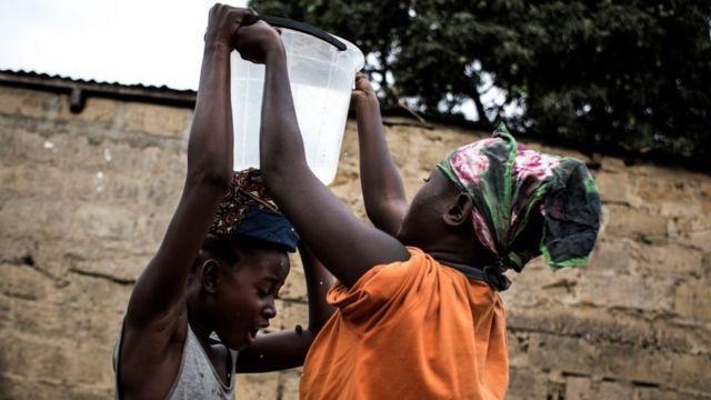 Mujeres con balde de agua en Kinshasa