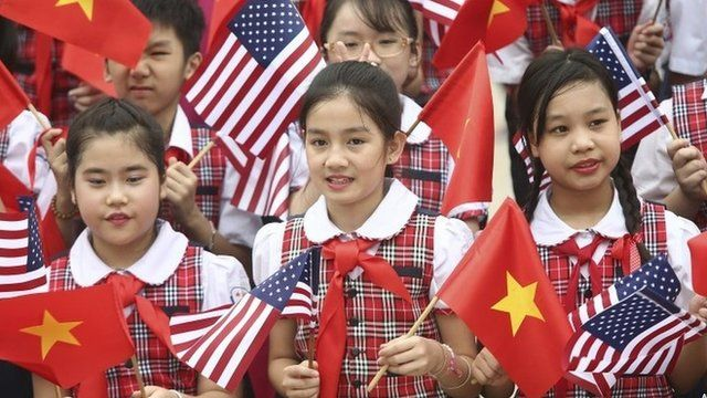 Vietnamese students hold US and Vietnamese flags at a welcoming ceremony for US President Barack Obama