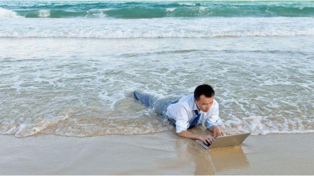 Homem chinês digita em computador à beira-mar