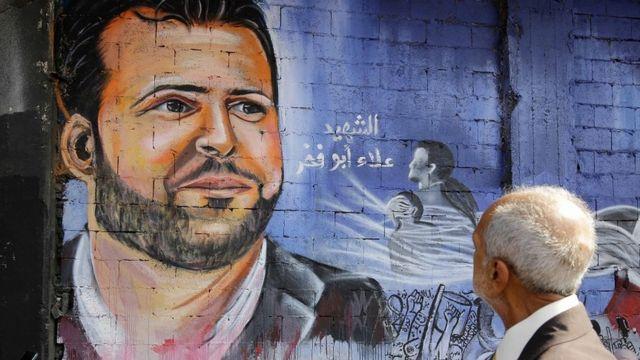 Un hombre mayor mira un mural de Abou Fakhr en la ciudad libanesa de Trípoli.