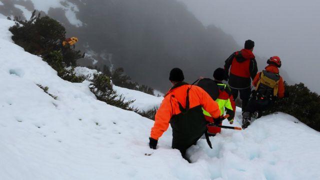 Спасатели в снегу на склоне горы