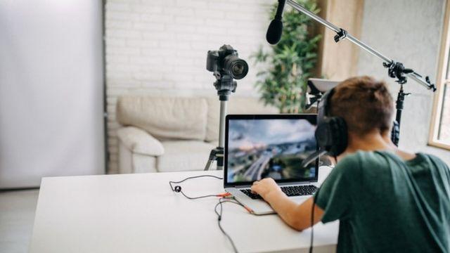Foto de um jovem fazendo a transmissão de um jogo de videogame