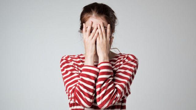 Mujer con ansiedad y miedo, tapándose la cara.