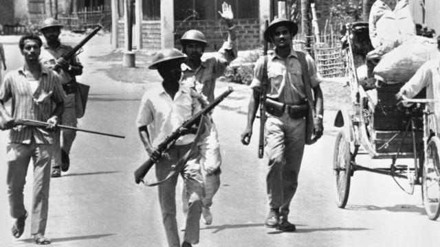 Uniformed East Pakistan rebel forces with armed civilians patrol a street in Jessore, East Pakistan on April 2, 1971