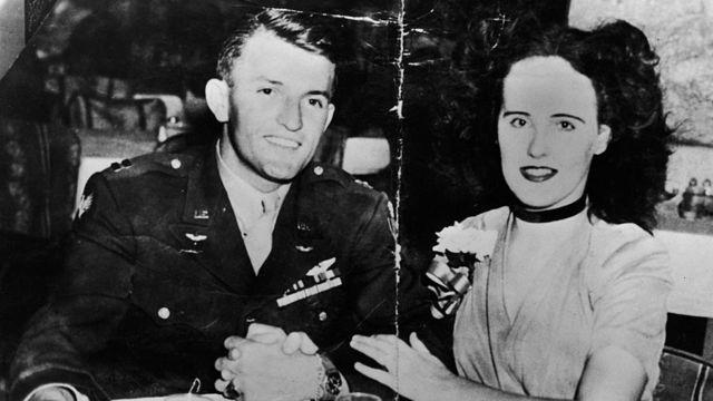 """Aspirante a actriz y víctima de asesinato de Elizabeth Short (1924 - 1947), conocida la 'Dalia Negra"""" se sienta cogida del brazo en una mesa de restaurante o bar con el soldado del Ejército estadounidense Major Matthew M. Gordon Jr. (- 1945), a mediados de 1940."""