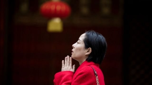 Mujer con manos juntas y lámpara detrás.