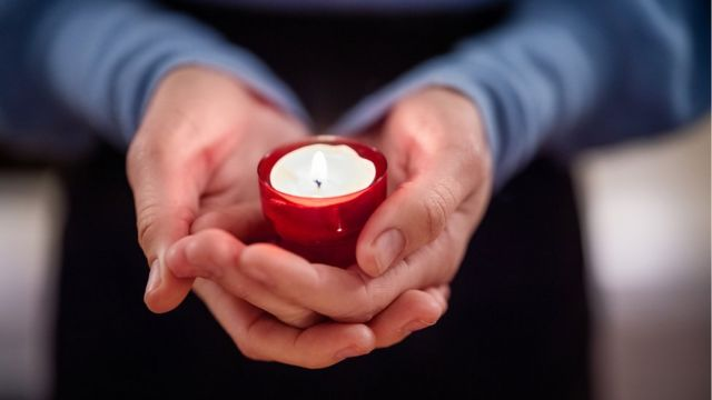 Mãos unidas segurando vela
