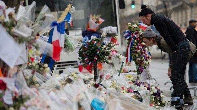 Members of Eagles of Death Metal look at floral tributes