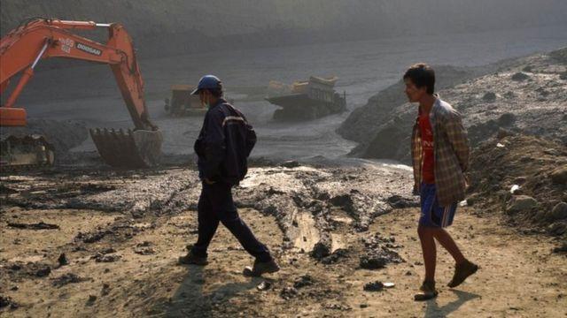 """بومیان در کنار """"دریاچه ای گلی"""" که در اثر رانش زمین تشکیل شده و معدنچیان را دفن کرد"""
