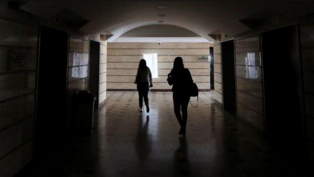 Dos mujeres caminan por un pasillo a oscuras en Caracas.