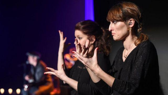 Переводчики расшифровывают выступление певца на языке жестов на фестивале в Сосайме, Франция, 23 марта 2017 года