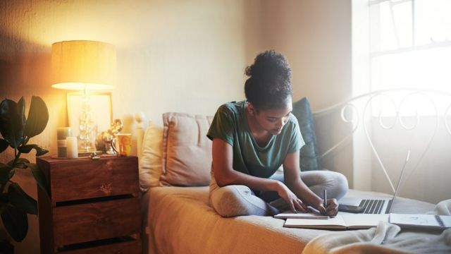 Una chica estudiando en la cama.