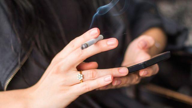 Fumar y chequear el celular