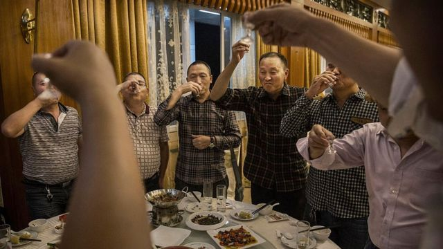 Chinese men toast each other and drink Moutai, the most famous wine called baijiu