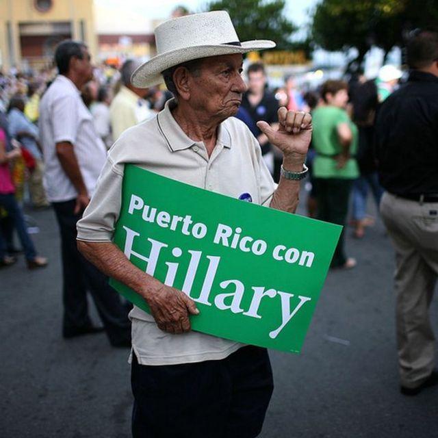 """Hombre con un cartel que dice: """"Puerto Rico con Hillary""""."""