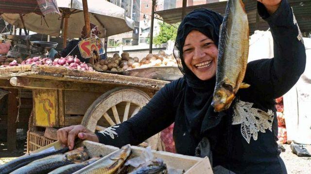 Una mujer sosteniendo un pescado