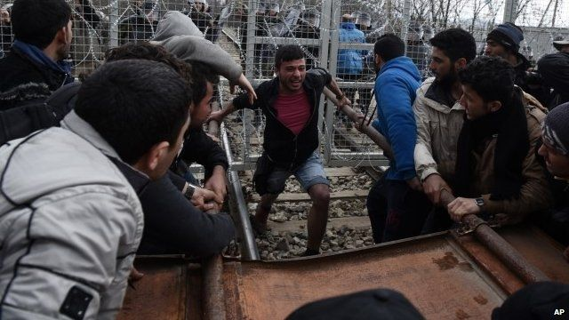 Refugees and migrants try to break an iron fence from the Greek side of the border as Macedonian police stand guard,