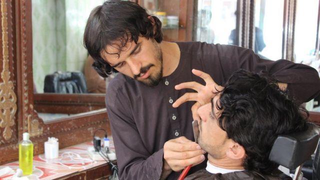 A hairdresser cuts off a customer's beard
