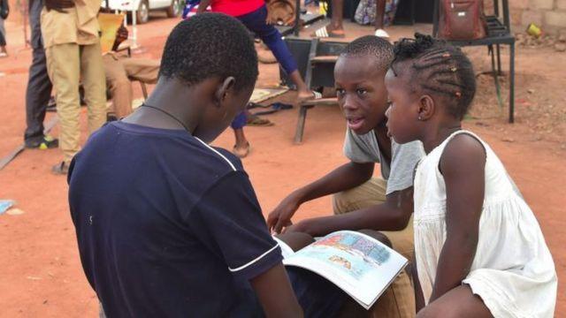Des enfants en train de lire des livres à la librairie nomade de la 10ème édition du festival 'Les Récréatrales' à Ouagadougou (Burkina Faso) - 2018