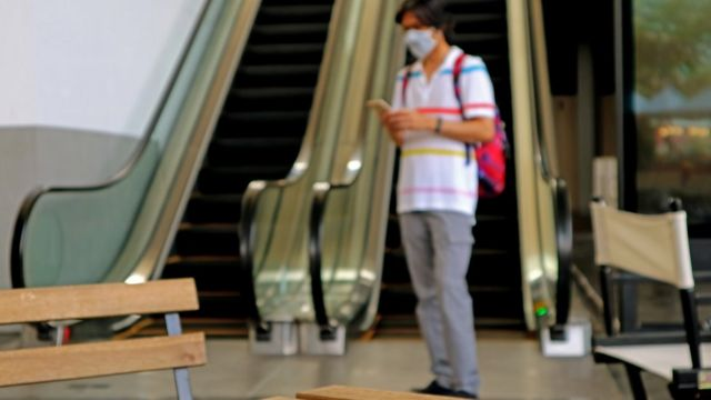 Homem usando máscara em frente a escada rolante
