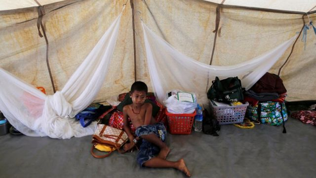 A Rakhine Buddhist boy who fled from recent violence in Maungdaw passes his time in a temporary shelter at a stadium in Sittwe