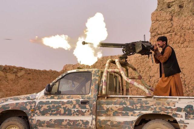 Боец антиталибского ополчения стреляет из пулемета в окрестностях Лашкаргаха
