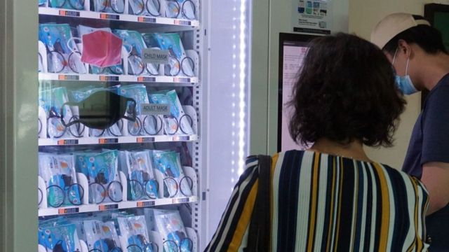 新加坡的一男一女在看着自动贩卖机中的口罩。