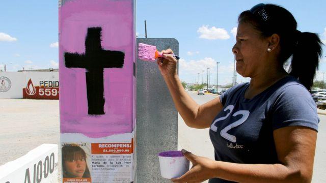 Una mujer pinta una cruz como parte de una campaña contra el feminicidio en Ciudad Juárez.