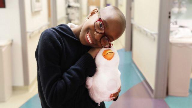 Menina em tratamento para câncer, careca e sorridente, de óculos, abraça seu pato-robô