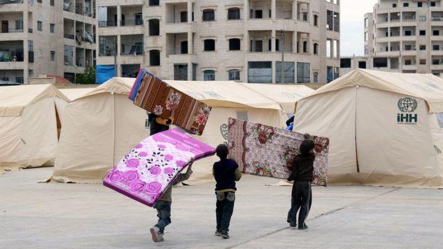 Niños sirios preparan las tiendas que acomodarán los civiles evacuados.