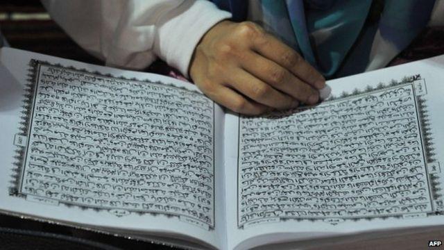 Uma mulher lê uma cópia do Corão