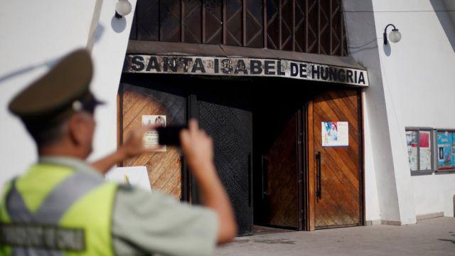 Полицейский фотографирует церковь в Сантьяго