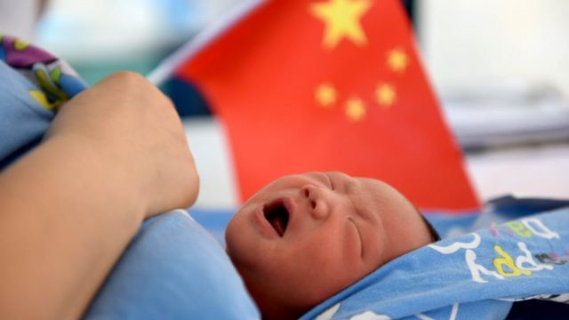 Chinese baby in front of Chinese flag