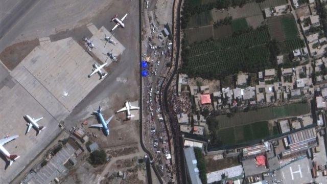 Imagem aérea mostra multidão e aviões