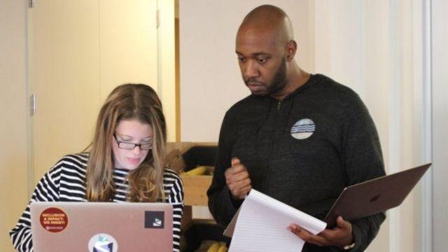 Una mujer y un hombre manejan un computador en una oficina.