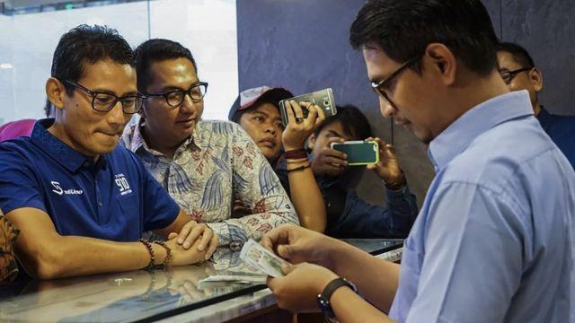 Bakal calon Wakil Presiden Sandiaga Uno (kiri) menukarkan uang dolar AS ke mata uang rupiah di Jakarta, Kamis (6/9). Sandiaga Uno menukarkan sebagian dolar AS miliknya sebagai upaya untuk menjaga nilai mata uang rupiah.