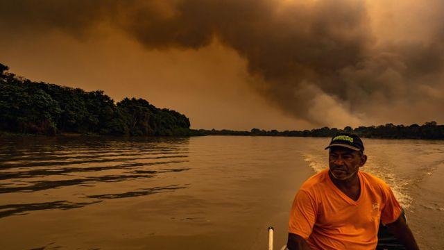Homem em um barco com fumaça de grandes proporções ao fundo