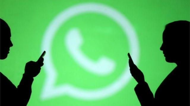 Pessoas usam celular com logo do WhatsApp ao fundo