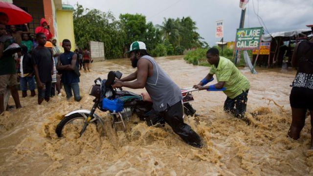 Hombres empujan una motocicleta en una zona inundada de Haití