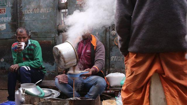 Pessoas comem na rua em Nova Déli, na Índia