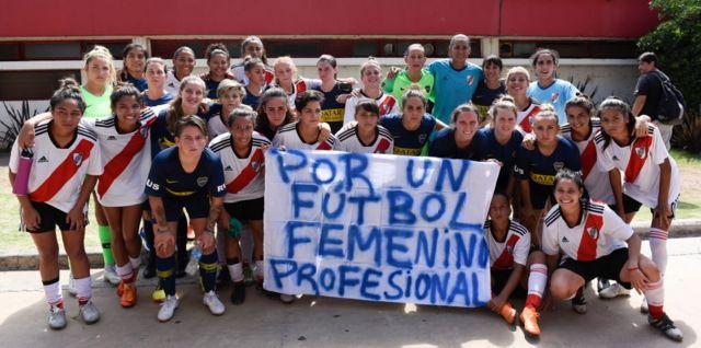 Jugadores de Boca Juniors y River Plate posan con una pancarta en favor del fútbol profesional femenino.