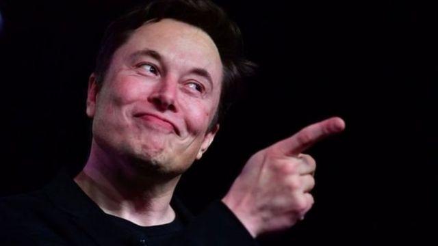 Retrato de Elon Musk com dedo em riste e sorriso sobre fundo preto