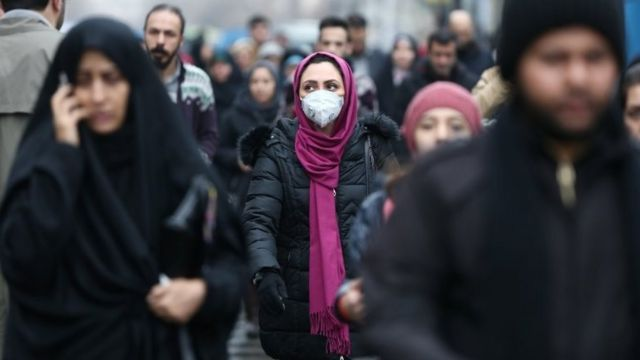 An Iranian woman wearing a protective mask to prevent contracting a coronavirus walks at Grand Bazaar in Tehran