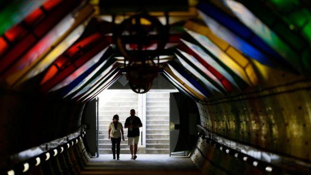 Una pareja camina por un túnel,