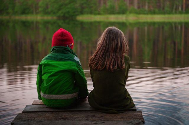 Dečak i devojčica sede na doku
