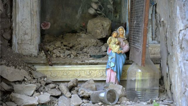 A Virgin Mary statue stands amid ruins in the Italian central town of Pescara del Tronto, on August 24, 2016