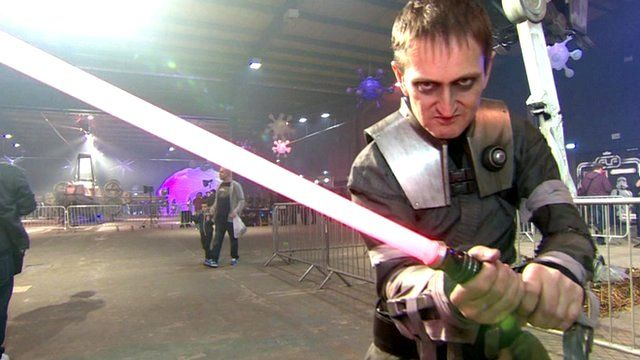 A man wearing a Star Wars outfit wields a toy lightsabre